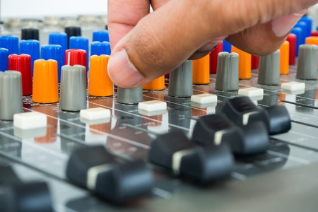 dubbing: Hand making adjustment on an audio soundboard Stock Photo
