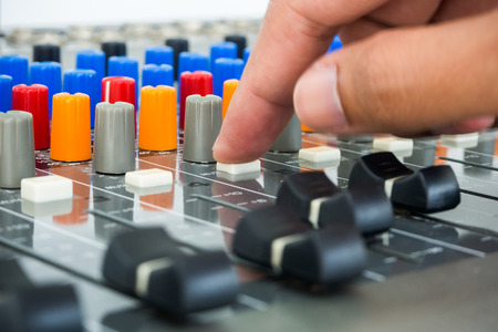 Hand making push button on an audio soundboard
