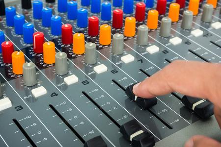 dubbing: Hand making slide on an audio soundboard