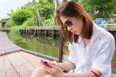 Woman using smartphone on a boat