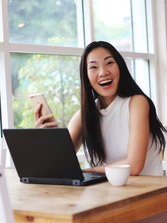 Beautiful Asian woman with long black hair got good news on her mobile phone and smile happily  , surprisingly to the camera. computer and cup of coffee on table.