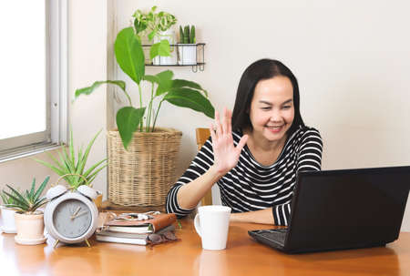 Asian woman sitting at wooden table decorated with houseplant , video chatting with laptop ,waving hand and smiling to person on screen.remote working or  working from home concept. Stockfoto