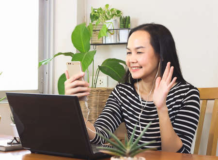 Asian woman sitting at wooden table decorated with houseplant , video chatting with mobile phone ,waving hand and smiling to person on screen.remote working or  working from home concept.