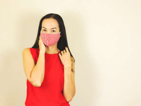 Beautiful Asian woman wearing red and white checkered hygienic mask and red no sleeve t-shirt,touching her cheek and hair  and looking at camera.Fashion and protection from covid-19 concept. Stock Photo