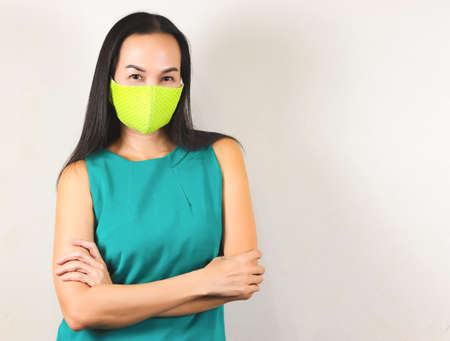 Beautiful Asian woman wearing polka dot green hygienic mask and green no sleeve t-shirt,crossing her arms and looking at camera.Fashion and protection from covid-19 concept.
