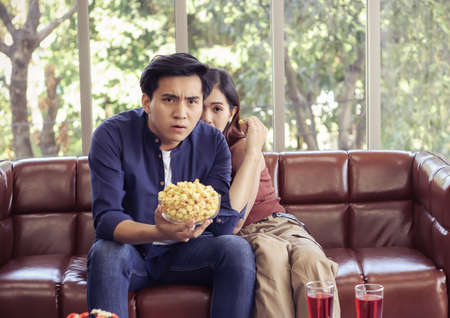 Attractive young Asian couple sitting on couch in living room , watching scary movie,a man holding popcorn in his hand while his girlfriend hiding behind him. Standard-Bild