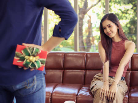 Beautiful and young Asian woman sitting on couch in living room looking and smiling  at her boyfriend who hide gift box behind.