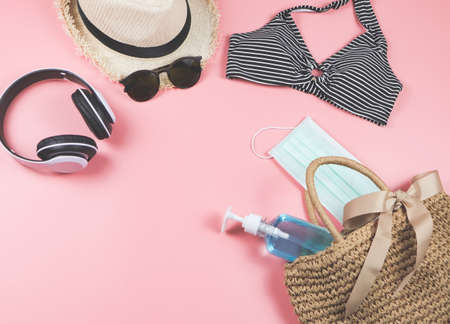 COVID-19 prevention , summer and new normal concept, top view of   bikini swim wear  and women's vacation accessories with surgical mask and sanitizer gel  in woven bag on pink background. Stock Photo