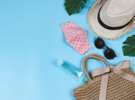 COVID-19 prevention , travel and new normal concept, top view of   woven bag with  sanitizer gel , pink polka dot fabric face mask  and women's vacation  accessories on blue  background. Stock Photo