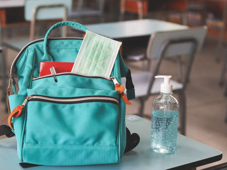 COVID-19 prevention , back to school and new normal concept.Front view of backpack with school supplies ,surgical mask and sanitizer gel on school desk in classroom.