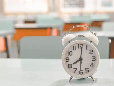 Education , back to school concept, selective focus.Closeup of vintage alarm clock with 8 o'clock on table in school classroom. starting class.