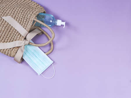 COVID-19 prevention , travel and new normal concept, top view of   woven bag with  sanitizer gel  and surgical  face masks  on purple  background with copy space.