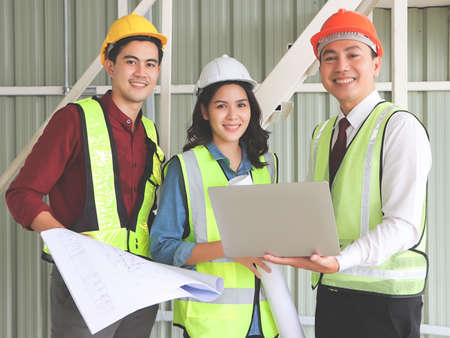 Portrait of three confident construction team, a female architect and two male engineers, wearing safety helmets,holding computer and blue print paper , smile and looking at camera.