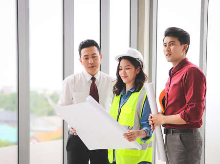 Group of three construction workers, one woman and two men standing by windows , holding blue print and discussing about project.