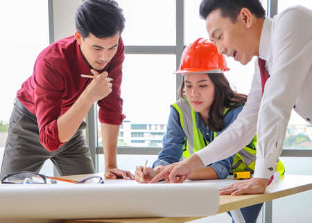 Three construction workers , a female architect and two male engineers discussing about the project at office table indoor.