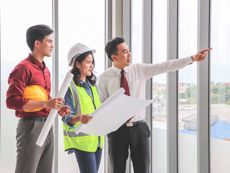 Group of three construction workers, one woman and two men standing by windows , holding blue print and discussing about project.Business man point out the window.