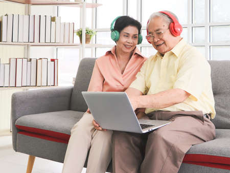 Happy Asian senior couple having good time together,sitting in living room , listening to the music from headphones with computer laptop on lap. Elderly lifestyle concept.