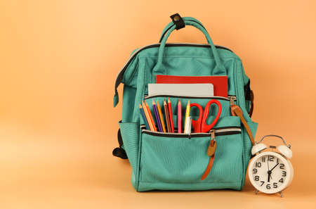 Front view  of  backpack with school supplies and vintage alarm clock  on orange background with copy space.Education and  back  to school  concept.