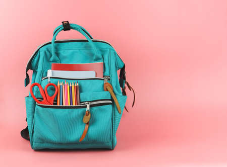 Front view of backpack with school supplies on pink background with copy space. Back to school and education concept.
