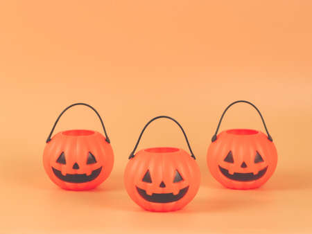 Front view  of Three Halloween pumpkin buckets  on orange background with copy space. Halloween holiday concept.