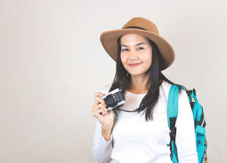 Portrait of Asian woman wearing white t-shirt and hat , holding camera and carrying backpack, smiling and looking at camera. Travelling concept.