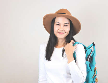 Portrait of Asian woman wearing white t-shirt and hat , and carrying backpack, smiling and looking at camera. Travelling concept.