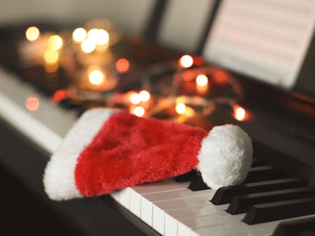 Front view of Christmas  Santa claus hat on electric piano keyboard with Christmas lights decoration  background. Christmas party music concept.selective focus 版權商用圖片