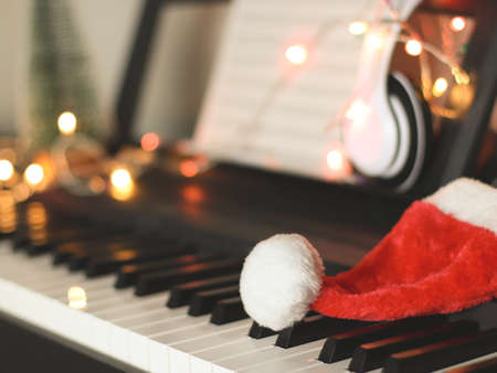 Front view of Christmas  Santa claus hat on electric piano keyboard with headphones and Christmas lights decoration  background. Christmas party music concept. selective focus