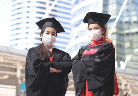 Two graduated women in graduation gowns and medical face masks, arms crossed and looking at camera. Graduation Class of 2020. Covid-19 prevention and new normal concept.