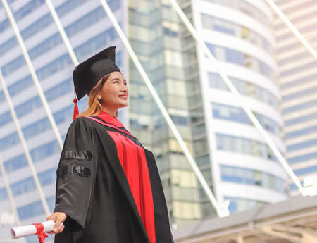 Happy Asian graduated women in graduation gowns , holding diploma, open arms, smiling and looking up. City building background. Education, successful concept.