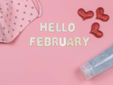 Top view or flat lay of wooden letters HELLO FEBRUARY with fabric mask, red glitter heart and alcohol sanitizer gel. new normal and Valentine's day.