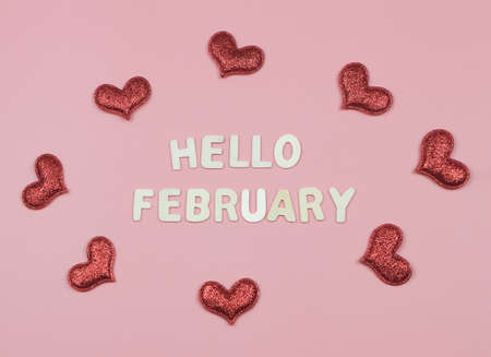 Top view or flat lay of wooden letters HELLO FEBRUARY with red glitter hearts on pink background. Greeting new month and Valentine's day. Standard-Bild