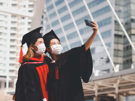Two graduated women in graduation gowns and medical face masks,  making selfie photo with mobile phone. Class of 2021. Covid-19 prevention and new normal concept. Imagens