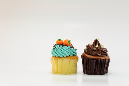 Dark chocolate and pumpkin face cupcakes on white background Stock Photo
