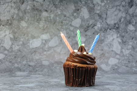Chocolate cupcake with three colourful candles. Stock Photo