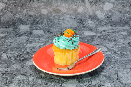 One Bluecream and Pumpkins on top of cupcakd on gray background