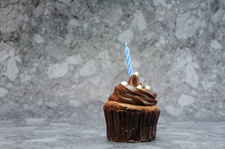 Chocolate cupcake with blue birthday candle.