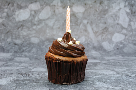 Chocolate cupcake with red birthday candle.