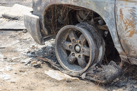 Close up front left wheel of a burnt car in fire situation insurance matter Stock Photo