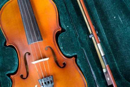 Detail of old fashioned violin on green velvet background. Stock Photo