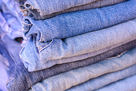 Close up stack of blue jeans background.