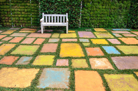 Wooden white bench in the park with colorful ground.