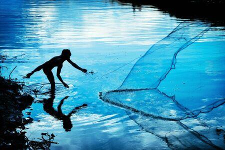 red: Un pescador swing su red para atrapar los fishs en el canal.