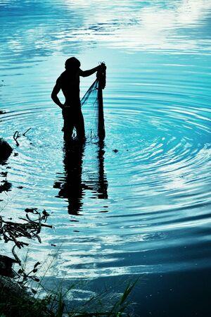 red: Un pescador prepair su red para atrapar fishs en el canal. Foto de archivo