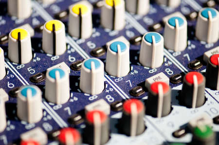 Closeup of colorful audio mixer board with selective focus.