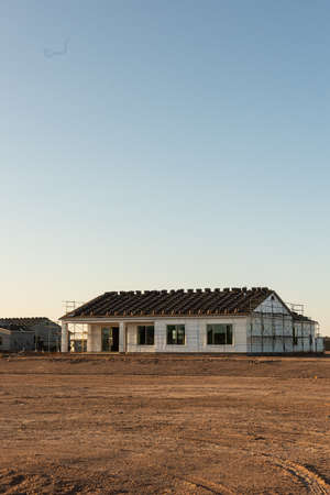 An unfinished house with roofing tiles stacked on the roof ready for placement stands next to other unfinished houses on a dirt lot in southwestern USA in a vertical view. Editorial