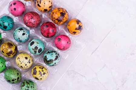 Colored quail eggs in box. Brightly colored quail eggs. Preparing for Easter