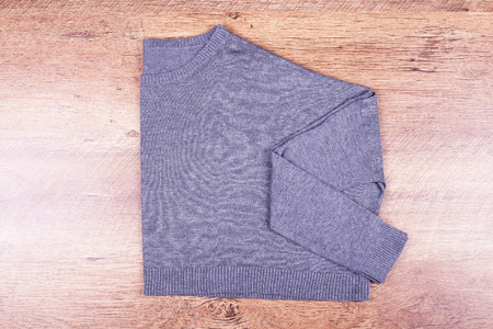 Stylish jacket on the laminate. Gray sweatshirt on the floor Stock Photo