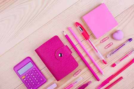 Pink notebook and office supplies. School creative desk, pink stationery. Wooden table with space to write text Imagens
