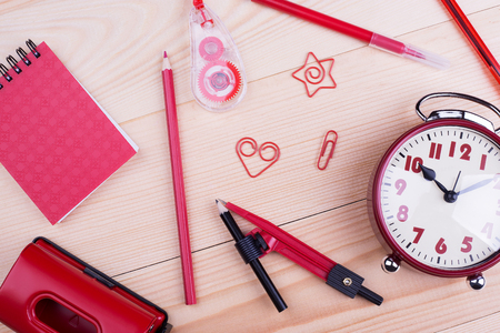 Red stationery objects close-up. School, office supplies on wood background. Colorful back to school concept.